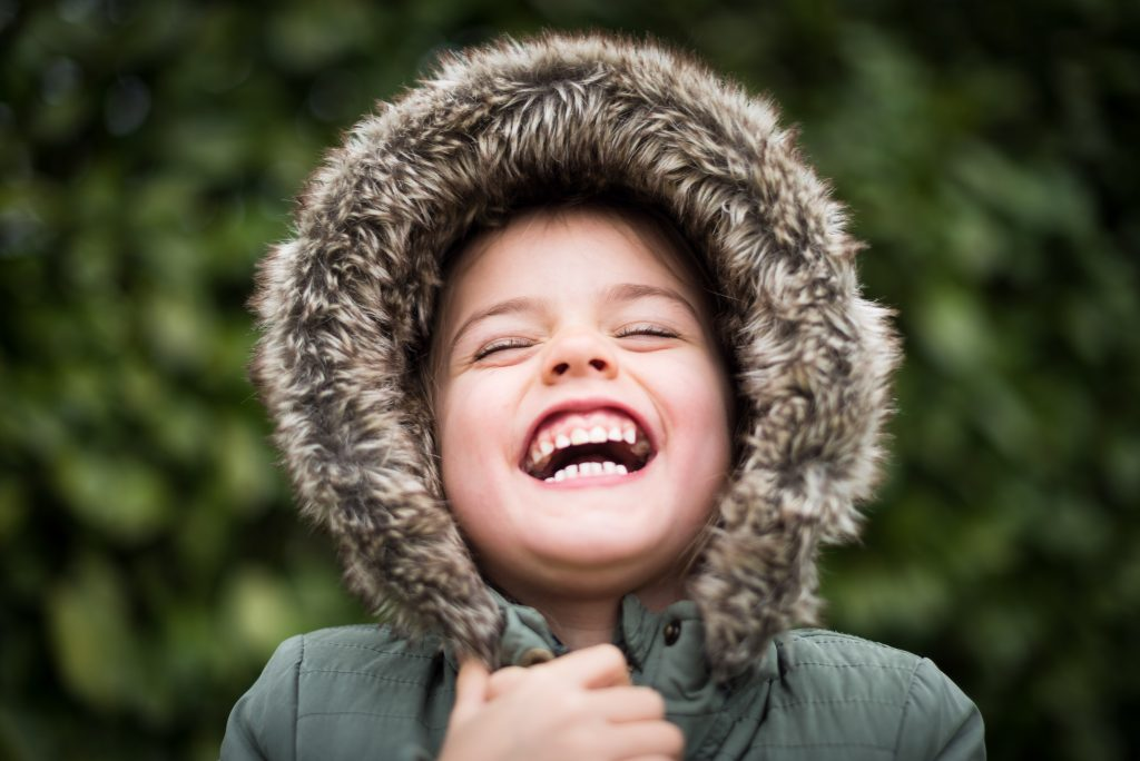 Young child in a winter coat looking up outside and smiling a wide, toothy smile.
