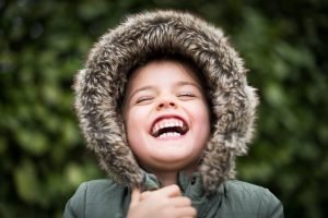 Young child in winter coat looking up outside and smiling a very wide, toothy smile.